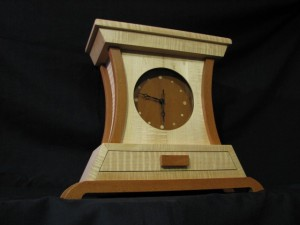 This tiger maple and lacewood solid wood clock by Ben Whitbeck Woodworking with its curved body and bold base with a small drawer would make a wonderful accent.  Ben can design your custom clock around the wood species and dimensions best suited to your home dĂŠcor.  CustomMade.com