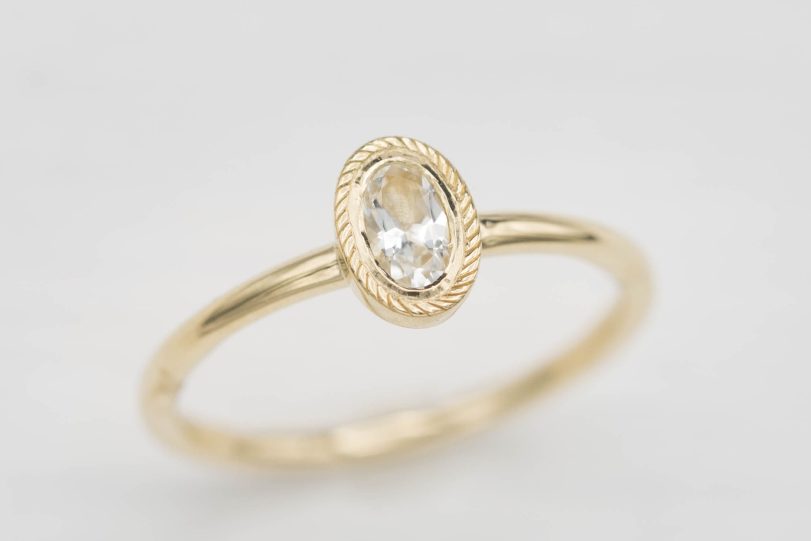 Oval white topaz in a delicate yellow gold bezel setting